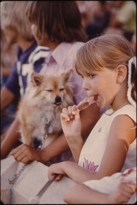 Youngster Unknowingly Has Shared Her Ice Cream Stick with the Dog as She Watches Judging During the Kiddies Parade in Johnson Park in New Ulm, Minnesota...
